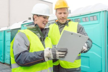 Workers doing some logistics in the rental toilet business looking at clipboard stock vector