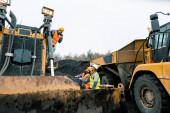 Těžké stroje a dělníci v lomu