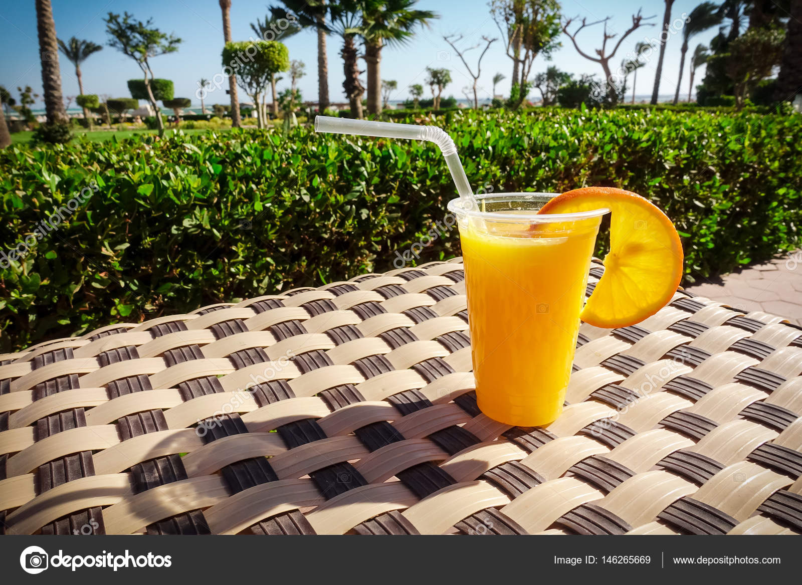 Jus d\'orange dans le verre en plastique sur la table avec ...