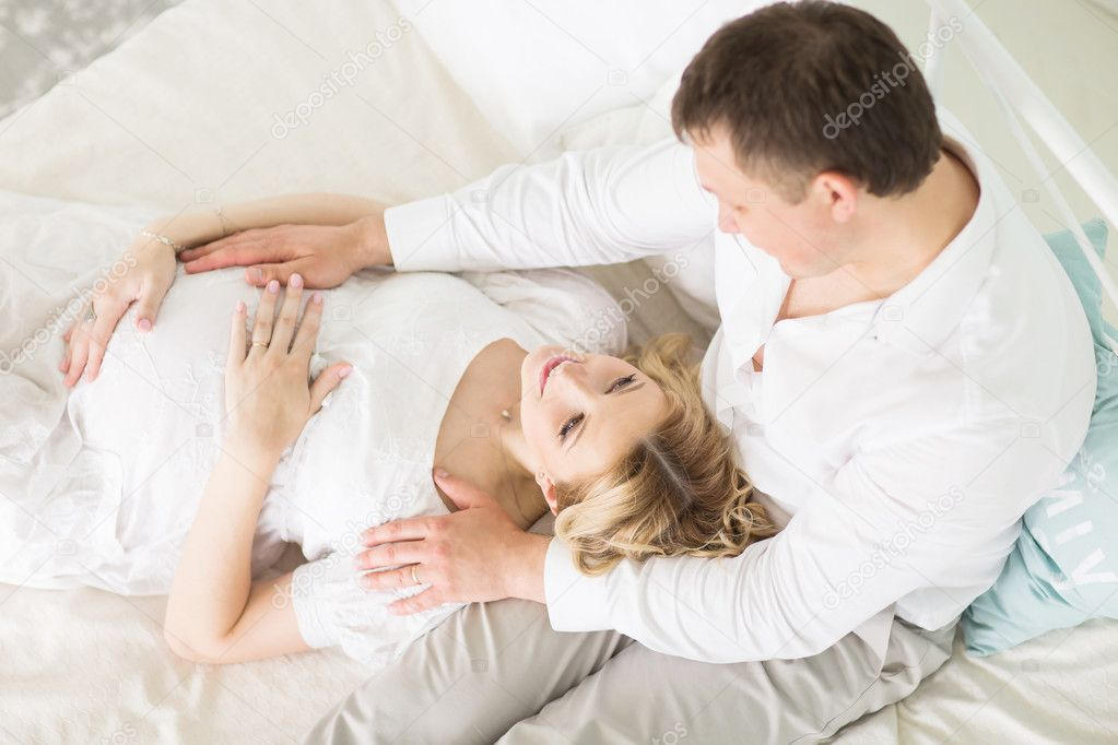 Loving husband and his pregnant wife on the bed in the bedroom    Stock  Photo. Loving husband and his pregnant wife on the bed in the bedroom