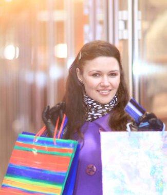 Beautiful girl with shopping walking down the street.