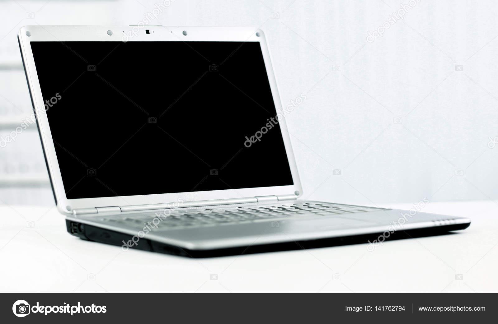 Portable argent dans un bureau moderne avec un écran noir pour du