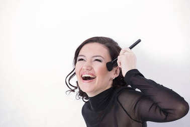 smiling young woman with brush for makeup.
