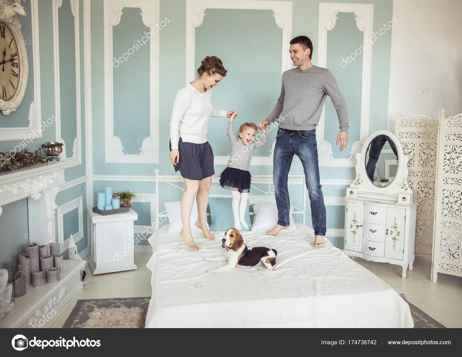 liefhebbende ouders spelen met baby dochter op bed in de slaapkamer foto van albertyurolaits