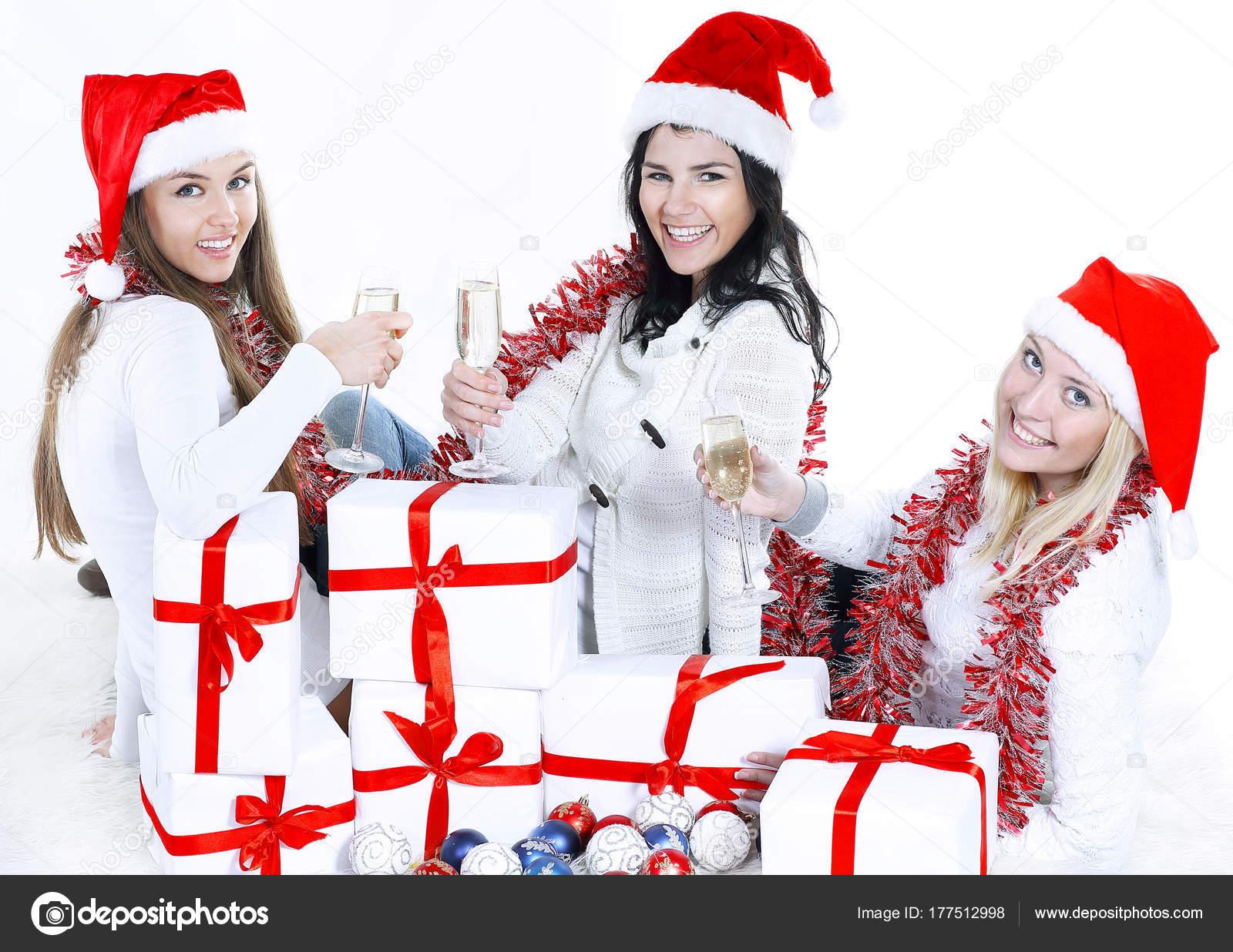 Closeup.Three junge Frauen in Hüte von Santa Claus Weihnachten ...