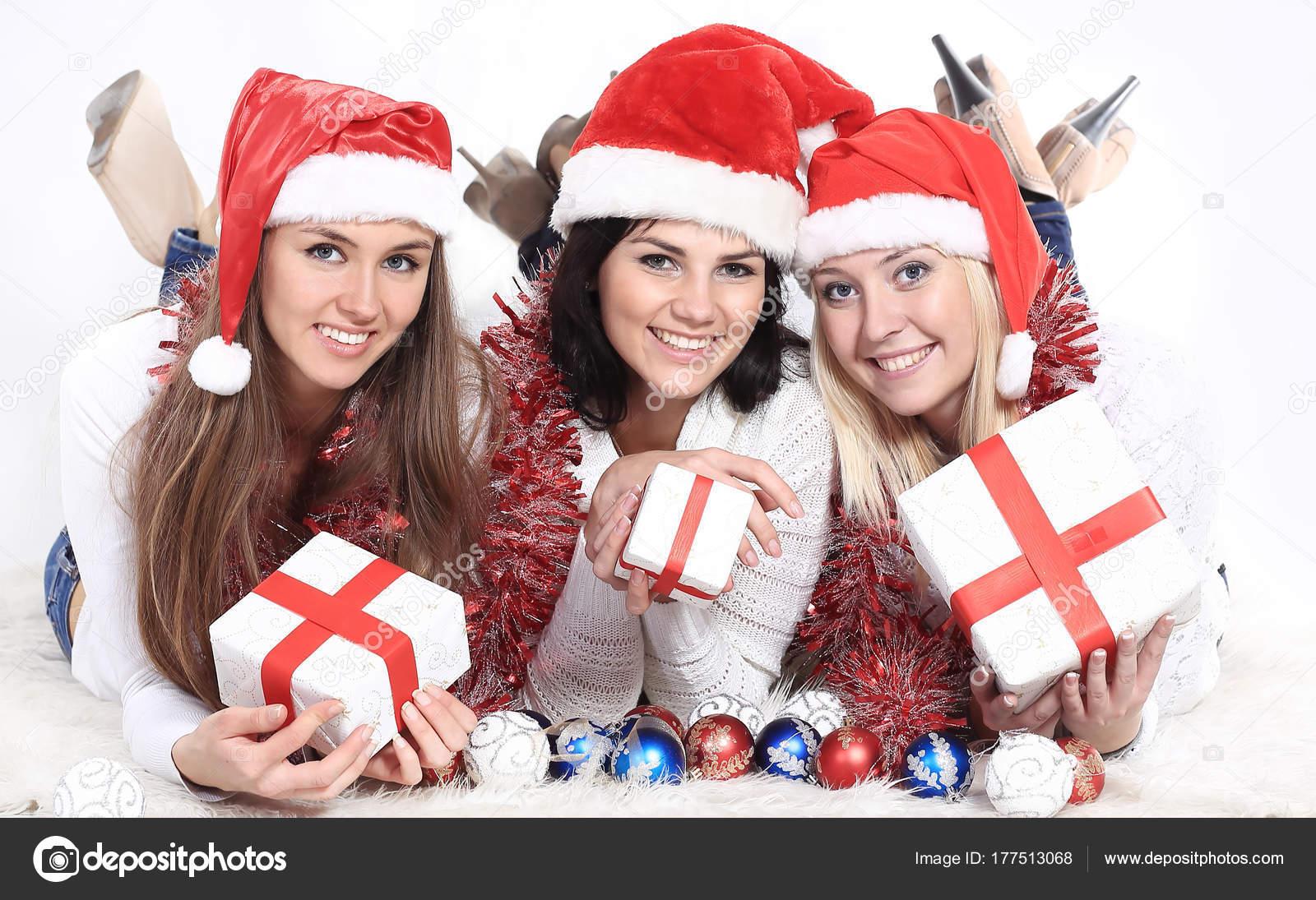 drei glückliche junge Frauen im Kostüm des Weihnachtsmannes mit ...