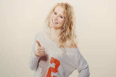 Beautiful young blond woman in jeans and t-shirt showing a thumbs up on