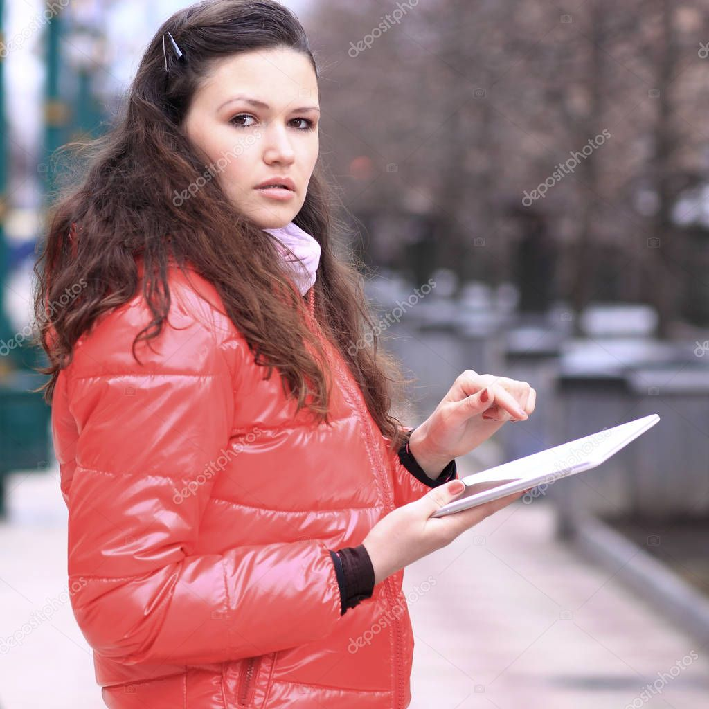 Beautiful girl with tablet in hands in the Park talking on social networks