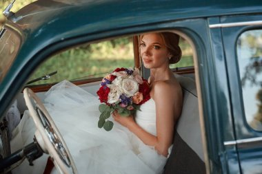 beautiful bride with wedding bouquet sitting in the car.