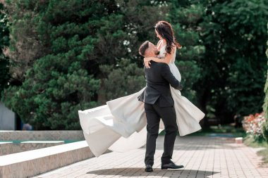 loving couple of newlyweds standing in city Park