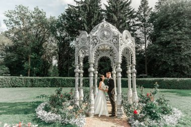 happy bride and groom standing in arched gazebo