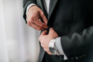 close up. groom buttoning his jacket. holidays and events
