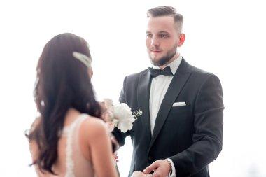 groom with wedding bouquet meeting his bride