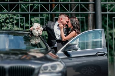 close up. bride and groom standing near the car