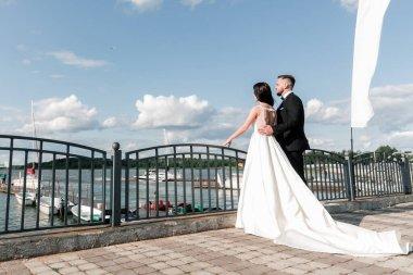 bride and groom standing on the bridge.