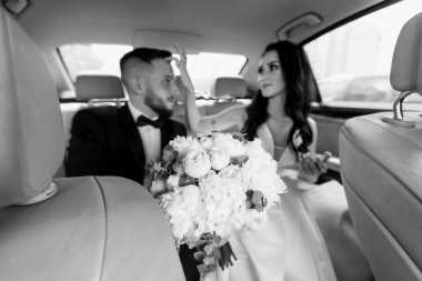 close up. happy bride and groom sitting in a chic car.