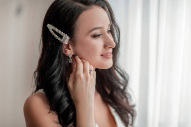 close up. girl bride trying on earrings.