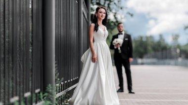 happy bride in wedding dress standing on city street