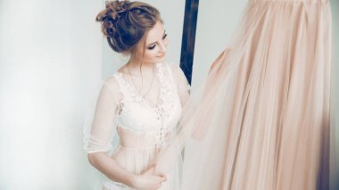 happy girl looking at her wedding dress