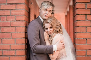 happy newlywed couple hugging each other while walking