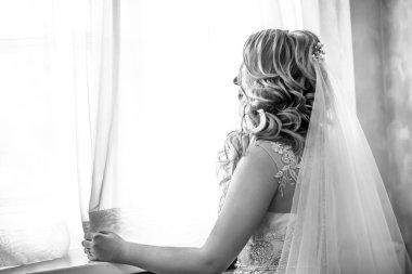close up. happy young woman bride looking through the window.