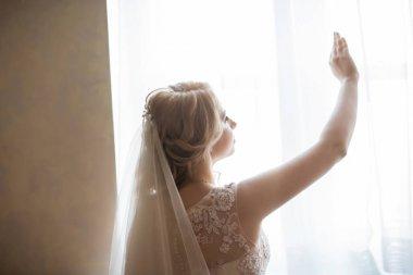 close up. happy girl bride opening window.