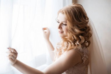 close up. young woman in wedding dress standing near the window.