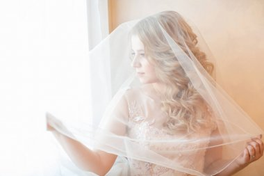 close up. beautiful young woman in wedding veil looking out the window.