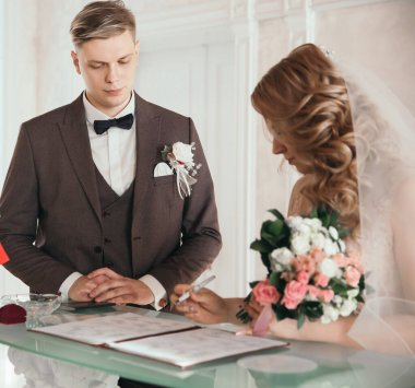close up. the happy couple by signing a marriage contract.