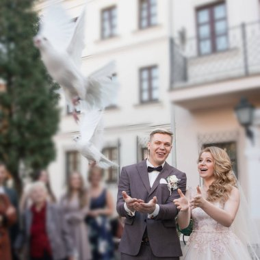close up. happy bride and groom releasing white doves