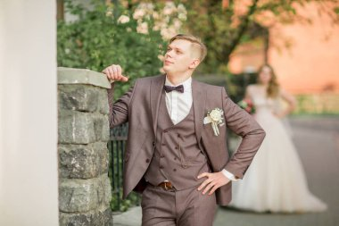 groom waiting for his bride standing on city street