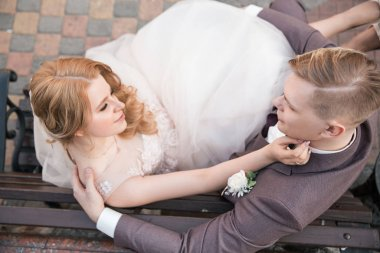 top view. happy bride and groom sitting on a bench