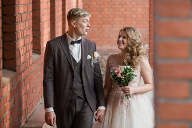 bride and groom standing in an old red brick building .