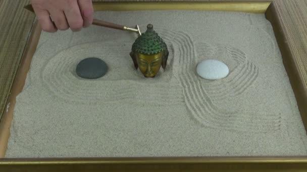 Člověk dělat malé pískové zen zahrada s mini hrábě