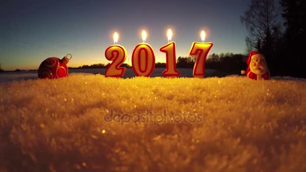 Šťastný nový rok 2017 - krásné svíčky na sněhu v zahradě, časová prodleva 4k