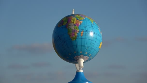 Small globe  map toy rotating on blue sky background, 4K