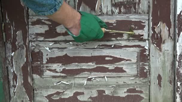 Mit Metallschaber alte braune Farbe von Holztür abkratzen