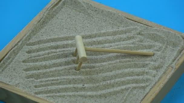 Rotující malé zen písek zahradní box s dřevěnou hrábě na modrém pozadí