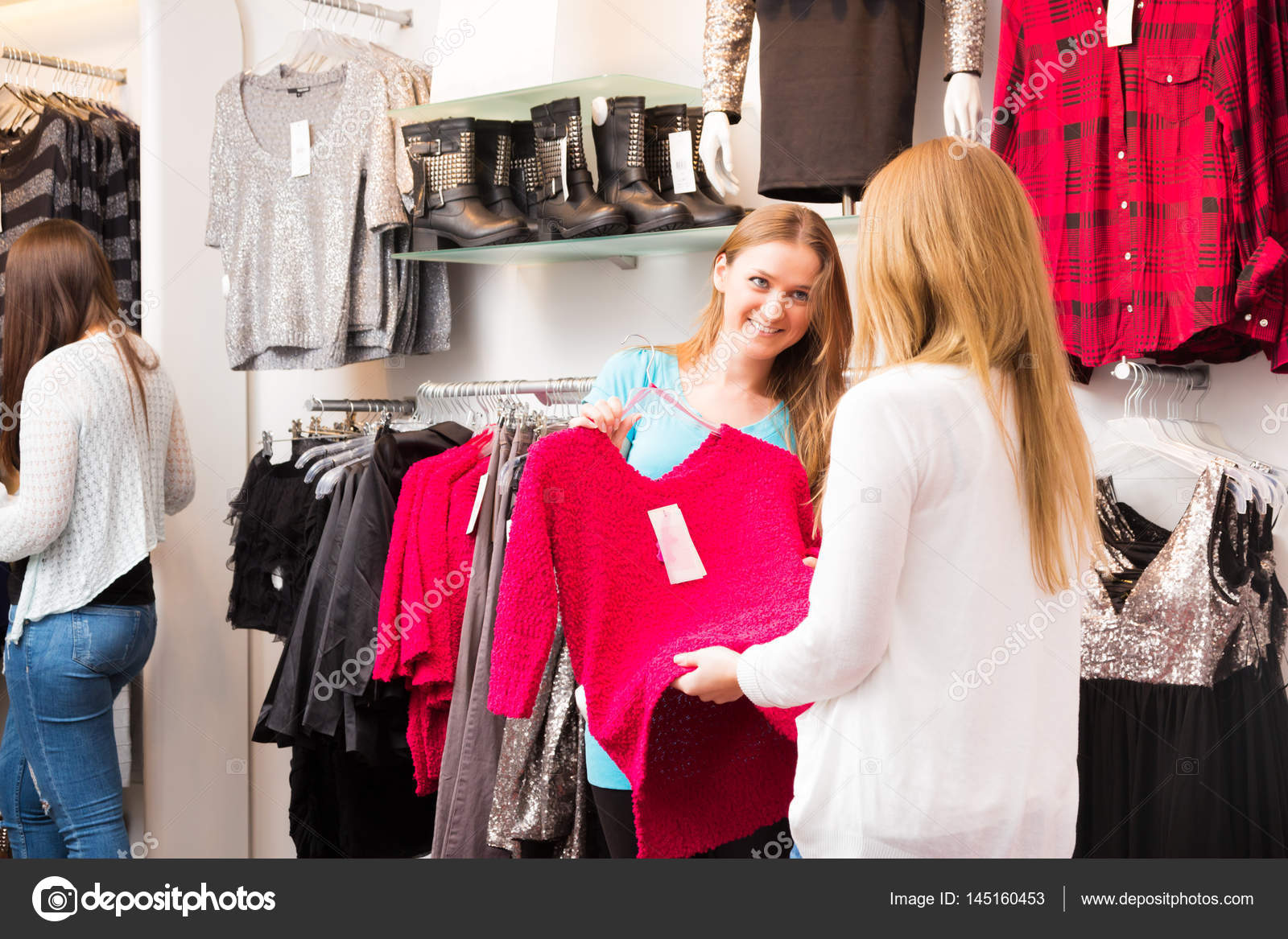 salesperson talking to customers in fashion store � stock