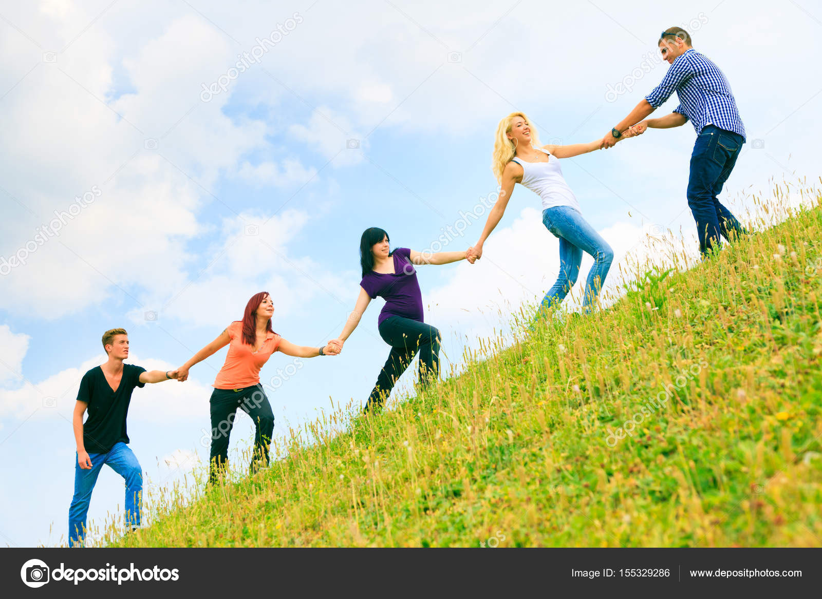 Helping Each Other: Young People Helping Each Other Climb A Hill