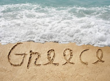 handwritten Greece text in sand