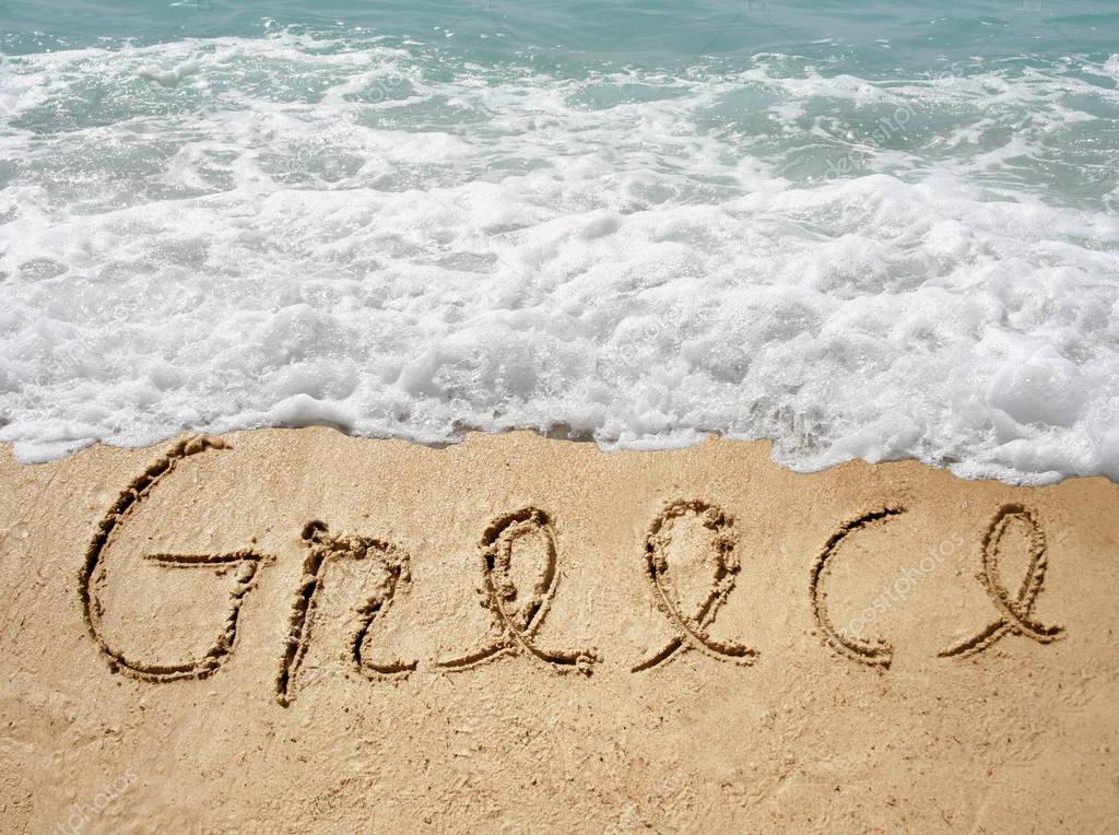 handwritten Greece text in sand