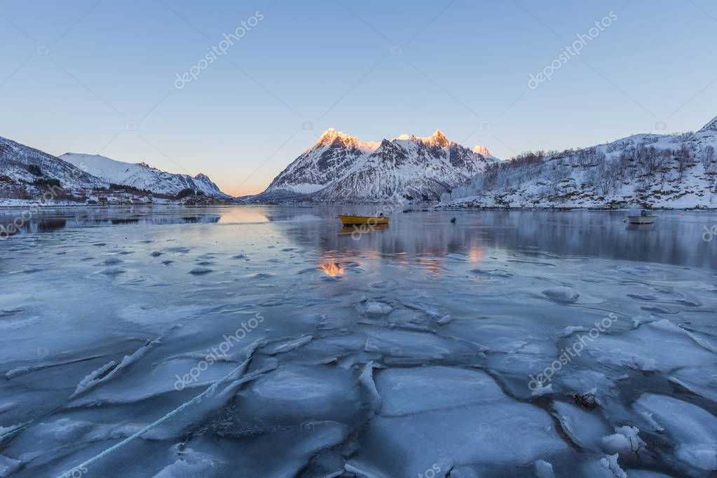 Winter scene of boat in partially frozen fjord and snowy mountai
