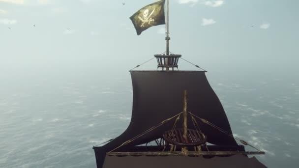 Egy öreg kalózhajó egy repülő kalóz zászlóval szántja fel az óceánt a kora reggeli ködös reggelen..