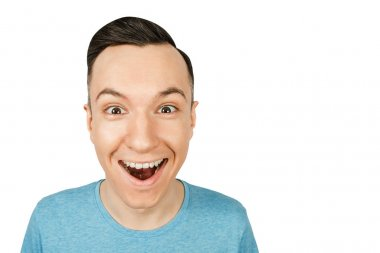 Close up portrait of young happy smiling guy, dressed in a blue t shirt on isolated white light background.