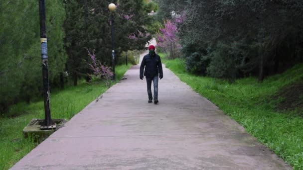 Man with red hat wearing mask and gloves walking towards the camera during covid 19 pandemic threat