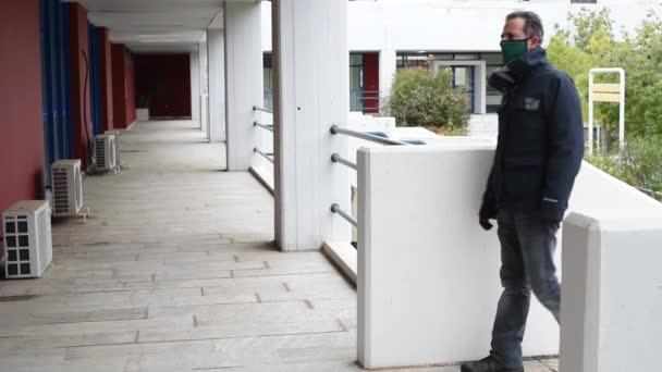 Man wearing his protective mask and gloves comes to an empty closed building- mask and gloves during covid 19 pandemic threat