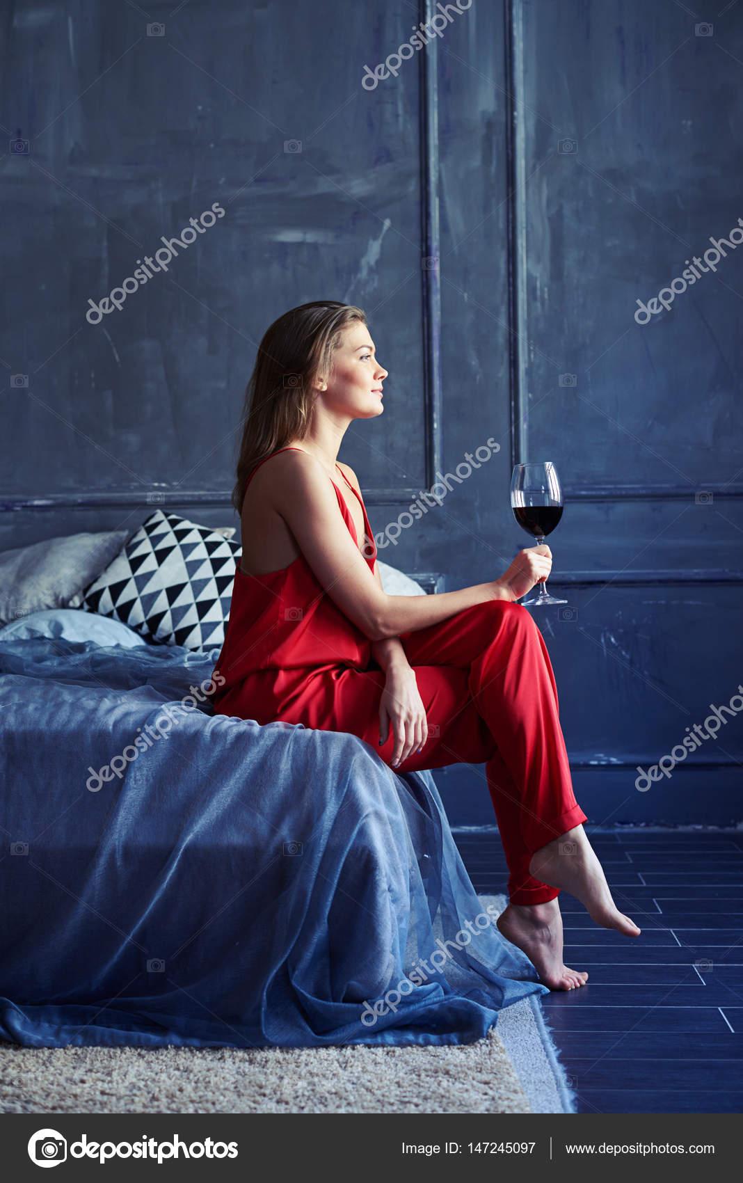 songeuse femelle avec un verre de vin rouge assis sur le. Black Bedroom Furniture Sets. Home Design Ideas