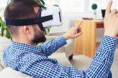 Fotografie Dark man with beard using VR glasses while sitting on sofa
