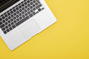 Flat lay of modern laptop keyboard on yellow background with copy space stock vector